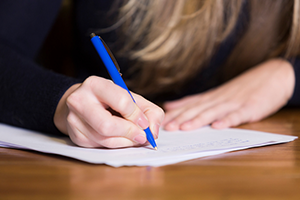 Image of person writing on paper